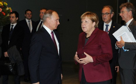 Merkel threatens Putin with more sanctions on Berlin visit