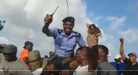 #EndSARS Protesters Lift Policeman In The Air, Celebrate Him For Saving Woman From Mob Attack In Abuja (Video)